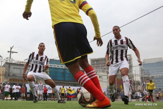An athlete of Colombia controls the ball during the Street Football World Cup in Sao Paulo, Brazil, on July 7, 2014. This sports event attracted around 300 youngsters from 20 countries and regions all over the world. Differing from the conventional football match, the Street Football World Cup allowed athletes of different sexes to play together and there are no arbitrators. (Xinhua/Rahel Patrasso)