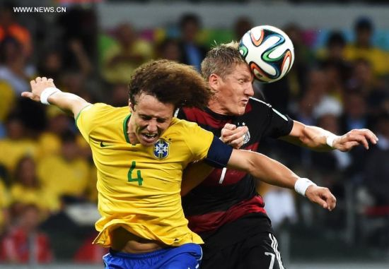 Brazil's David Luiz competes for a header with Germany's Bastian Schweinsteiger during a semifinal match between Brazil and Germany of 2014 FIFA World Cup at the Estadio Mineirao Stadium in Belo Horizonte, Brazil, on July 8, 2014.(Xinhua/Li Ga)