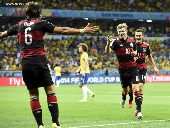 Germany's Miroslav Klose (R) and Sami Khedira (L) celebrate with Toni Kroos (C) for Toni's second goal during a semifinal match between Brazil and Germany of 2014 FIFA World Cup at the Estadio Mineirao Stadium in Belo Horizonte, Brazil, on July 8, 2014.(Xinhua/Qi Heng)