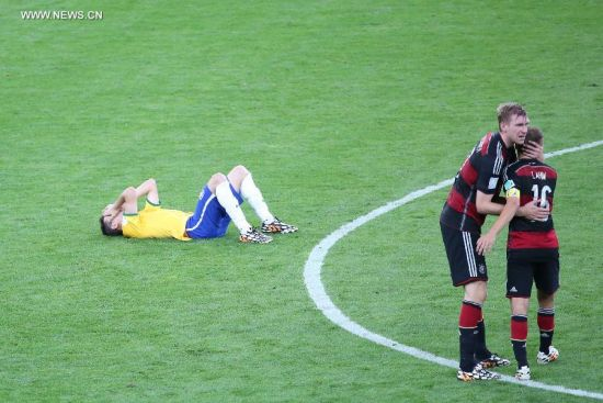 Brazil's Oscar (L) lies on the field after a semifinal match between Brazil and Germany of 2014 FIFA World Cup at the Estadio Mineirao Stadium in Belo Horizonte, Brazil, on July 8, 2014. Germany won 7-1 over Brazil and qualified for the final on Tuesday.(Xinhua/Li Ming)