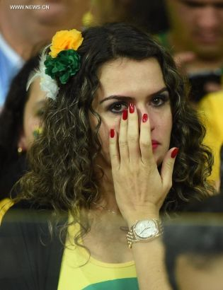 A Brazil's supporter wipes her tears during a semifinal match between Brazil and Germany of 2014 FIFA World Cup at the Estadio Mineirao Stadium in Belo Horizonte, Brazil, on July 8, 2014.(Xinhua/Liu Dawei)