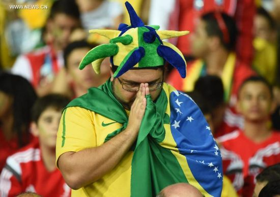 A Brazil's supporter prays during a semifinal match between Brazil and Germany of 2014 FIFA World Cup at the Estadio Mineirao Stadium in Belo Horizonte, Brazil, on July 8, 2014.(Xinhua/Liu Dawei)