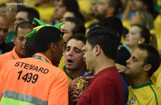 Brazil's supporters argue with security members during a semifinal match between Brazil and Germany of 2014 FIFA World Cup at the Estadio Mineirao Stadium in Belo Horizonte, Brazil, on July 8, 2014.(Xinhua/Liu Dawei)