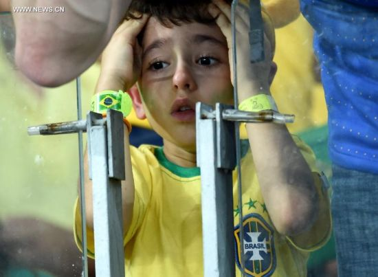 A Brazil's fan reacts while watching a semifinal match between Brazil and Germany of 2014 FIFA World Cup at the Estadio Mineirao Stadium in Belo Horizonte, Brazil, on July 8, 2014.(Xinhua/Li Ga)