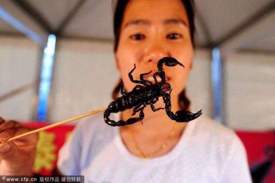A woman holds a cooked scorpian