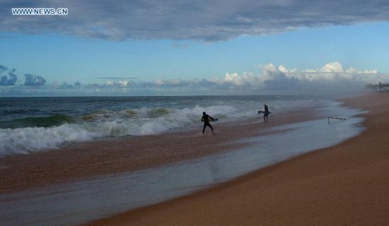Two divers get ready to go into the sea early in the morning in Salvador, Brazil, on July 2, 2014. (Xinhua/Cao Can)