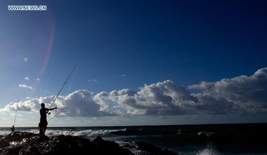 Local residents fish in the early morning on a seaside rock in Salvador, Brazil, on July 3, 2014. (Xinhua/Cao Can)