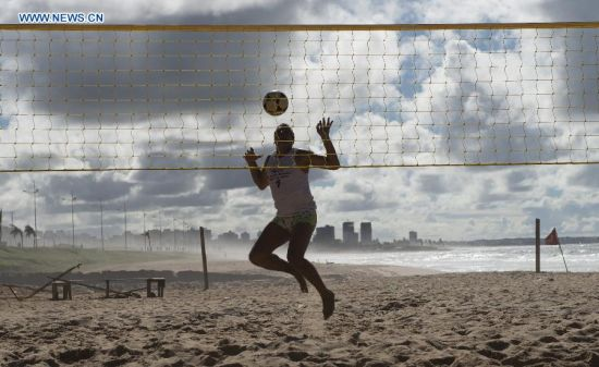 A foot volleyball fan jumps for the ball in the early morning on a beach in Salvador, Brazil, on July 2, 2014. (Xinhua/Yang Lei)