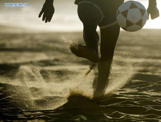 A man plays foot volleyball in the early morning on a beach in Salvador, Brazil, on July 4, 2014. (Xinhua/Yang Lei)