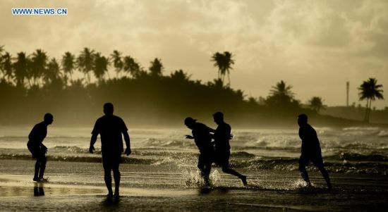People play football in the early morning on a beach in Salvador, Brazil, on July 6, 2014. (Xinhua/Yang Lei)