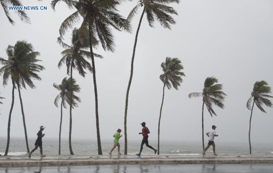 People jog on a seaside path in the early morning on a beach in Salvador, Brazil, on July 5, 2014. (Xinhua/Yang Lei)