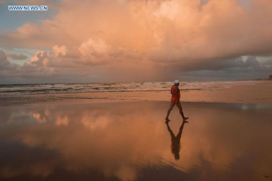 A man walks in the early morning on a beach in Salvador, Brazil, on July 7, 2014. (Xinhua/Yang Lei)