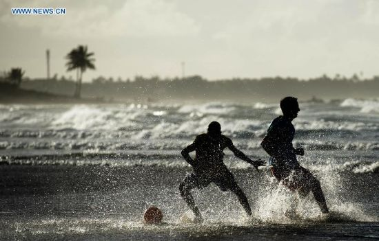 Two men vie for a football in the early morning on a beach in Salvador, Brazil, on July 6, 2014. (Xinhua/Yang Lei)