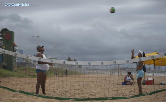 People play volleyball in the early morning on a beach in Salvador, Brazil, on July 5, 2014. (Xinhua/Yang Lei)