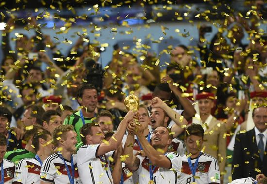 Germany's team players hold up the World Cup trophy as they celebrate after winning the 2014 FIFA World Cup final football match between Germany and Argentina 1-0 following extra-time at the Maracana Stadium in Rio de Janeiro, Brazil, on July 13, 2014.