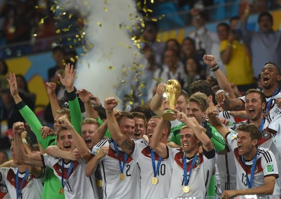 Germany's defender and captain Philipp Lahm (front-2R) holds up the World Cup trophy as he celebrates with his teammates after winning the 2014 FIFA World Cup final football match between Germany and Argentina 1-0 following extra-time at the Maracana Stadium in Rio de Janeiro, Brazil, on July 13, 2014.