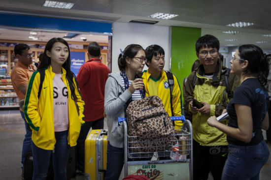 """Xiang Chen (R 2) and his wife Wang Jialing (R 4) got acquainted with Zhang Qiao (R 3) and Yingying (R 6) through the online discussion group """"Break the bank to watch World Cup."""" They arrived Brasilia at 9 am July 12 taking the same flight. At the airport, the two couples met with the staff from the hotel that they booked for the night."""