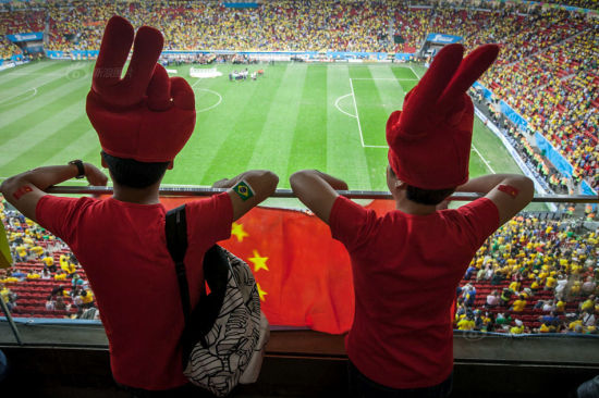 Two people wearing red clothes and Chinese-national-flag-printed decorations caught the eyes of many foreign football fans, who asked to take photos with them.