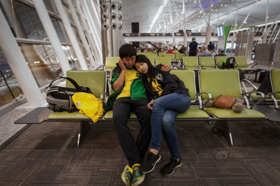 Zhang Qiao and Yingying waited for their flight for Rio de Janeiro at the airport at 11 pm. They planned to sleep at Rio's airport till the next noon after they arrived, then they could check in the hotel and watch the final at Maracana Stadium. Finally, they would go back to China after having a rest in Rio for a few days.
