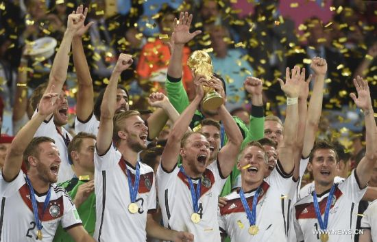 Germany's Benedikt Howedes (C, front) holds the FIFA World Cup trophy as Germany's players celebrate their victory after the final match between Germany and Argentina of 2014 FIFA World Cup at the Estadio do Maracana Stadium in Rio de Janeiro, Brazil, on July 13, 2014. Germany won 1-0 over Argentina after 120 minutes and took its fourth World Cup title on Sunday. (Xinhua/Yang Lei)
