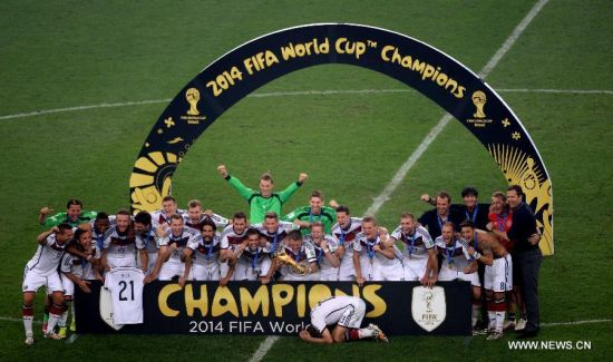 Germany's players pose with the World Cup trophy after the final match between Germany and Argentina of 2014 FIFA World Cup at the Estadio do Maracana Stadium in Rio de Janeiro, Brazil, on July 13, 2014. Germany won 1-0 over Argentina after 120 minutes and took its fourth World Cup title on Sunday. (Xinhua/Li Ga)