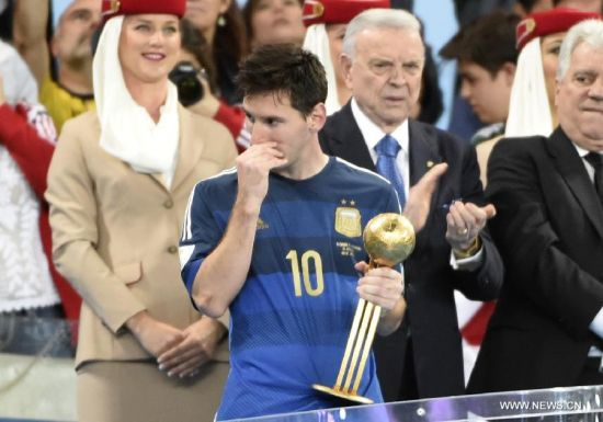 Argentina's Lionel Messi (front) reacts as being presented the Golden Ball trophy after the final match between Germany and Argentina of 2014 FIFA World Cup at the Estadio do Maracana Stadium in Rio de Janeiro, Brazil, on July 13, 2014. Germany won 1-0 over Argentina after 120 minutes and took its fourth World Cup title on Sunday. (Xinhua/Yang Lei)