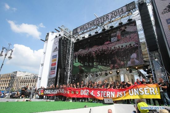 German football players hold a banner on stage during a celebration to mark the team's 2014 Brazil World Cup victory in Berlin, Germany, July 15, 2014. Germany's team returned home on Tuesday after winning the 2014 Brazil World Cup. (Xinhua/Zhang Fan)