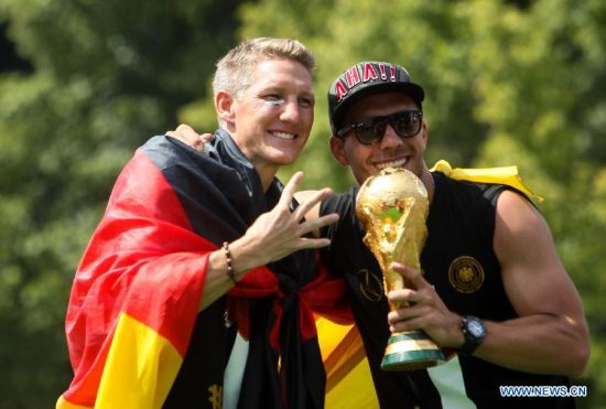 German football players Lukas Podolski (R) and Bastian Schweinsteiger pose during celebration to mark the team's 2014 Brazil World Cup victory in Berlin, Germany, July 15, 2014. Germany's team returned home on Tuesday after winning the 2014 Brazil World Cup. (Xinhua/Zhang Fan)