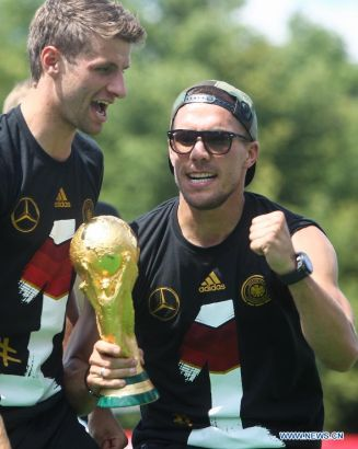 German football players Lukas Podolski (R) and Thomas Mueller celebrate on stage during celebration to mark the team's 2014 Brazil World Cup victory in Berlin, Germany, July 15, 2014. Germany's team returned home on Tuesday after winning the 2014 Brazil World Cup. (Xinhua/Zhang Fan)