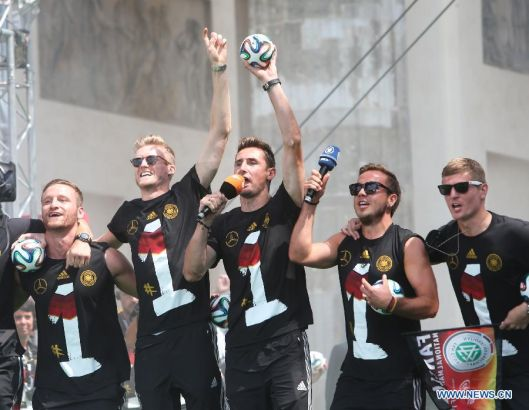 German football players Andre Schuerrle (L2), Miroslav Klose (C), Mario Goetze (R2) and Toni Kroos (R) wave to supporters during celebration to mark the team's 2014 Brazil World Cup victory in Berlin, Germany, July 15, 2014. Germany's team returned home on Tuesday after winning the 2014 Brazil World Cup. (Xinhua/Zhang Fan)