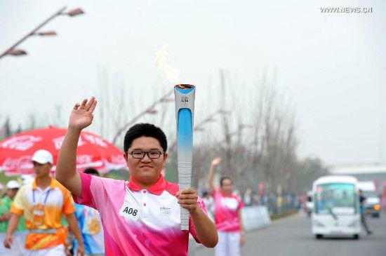 Torch bearer Wang Wei holds the flame during the torch relay of Nanjing 2014 Youth Olympic Games in Nanjing, capital of east China's Jiangsu Province, on Aug.12, 2014. Nanjing 2014 Youth Olympic Games will be held from August 16 to 28.(Xinhua/Li Xiang)
