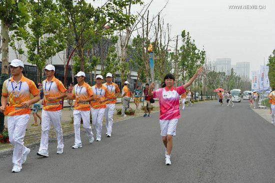 Torch bearer Li Yiting holds the flame during the torch relay of Nanjing 2014 Youth Olympic Games in Nanjing, capital of east China's Jiangsu Province, on Aug.12, 2014. Nanjign 2014 Youth Olympic Games will be held from August 16 to 28.(Xinhua/Li Xiang)