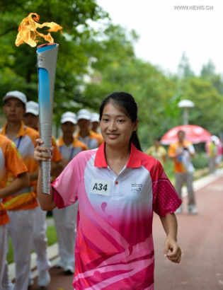 Torch bearer Peng Huijin holds the Olympic torch during the torch relay of the Nanjing 2014 Youth Olympic Games in Nanjing, capital of east China's Jiangsu Province, on Aug.12, 2014.The Nanjing 2014 Youth Olympic Games will be held from August 16 to 28. (Xinhua/Li Xiang)