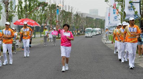 Torch bearer Wang Yu holds the flame during the torch relay of Nanjing 2014 Youth Olympic Games in Nanjing, capital of east China's Jiangsu Province, on Aug.12, 2014. Nanjing 2014 Youth Olympic Games will be held from August 16 to 28. (Xinhua/Li Xiang)