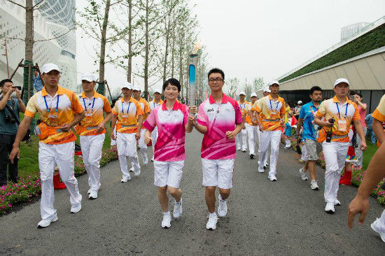 Torch bearer Hou Kun and Wu Jingyu(L) hold the flame during the torch relay of Nanjing 2014 Youth Olympic Games in Nanjing, capital of east China's Jiangsu Province, on Aug.12, 2014. The Nanjing 2014 Youth Olympic Games will be held from August 16 to 28.(Xinhua/Li Xiang)