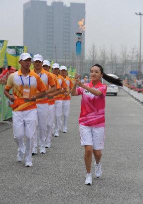 Torch bearer Liu Yige holds the flame during the torch relay of Nanjing 2014 Youth Olympic Games in Nanjing, capital of east China's Jiangsu Province, on Aug.12, 2014. The Nanjing 2014 Youth Olympic Games will be held from August 16 to 28.(Xinhua/Li Xiang)