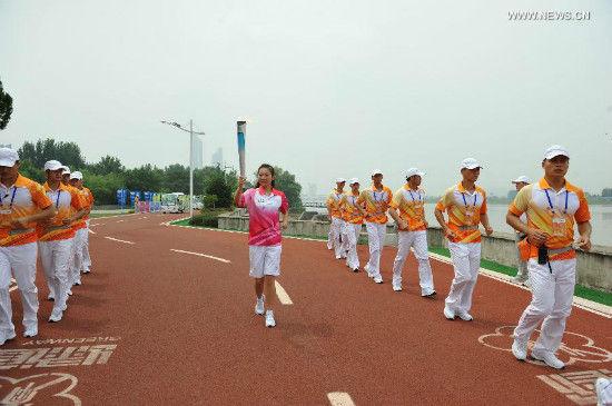 Torch bearer Yang Li holds the flame during the torch relay of Nanjing 2014 Youth Olympic Games in Nanjing, capital of east China's Jiangsu Province, on Aug.12, 2014. The Nanjing 2014 Youth Olympic Games will be held from August 16 to 28.(Xinhua/Li Xiang)