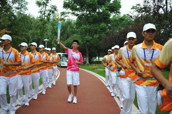 Torch bearer Zhang Qirui holds the flame during the torch relay of Nanjing 2014 Youth Olympic Games in Nanjing, capital of east China's Jiangsu Province, on Aug.12, 2014. Nanjing 2014 Youth Olympic Games will be held from August 16 to 28.(Xinhua/Li Xiang)