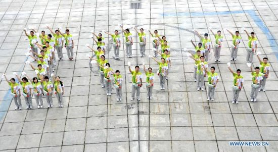 Volunteers of Nanjing 2014 Youth Olympic Games line in the shape of
