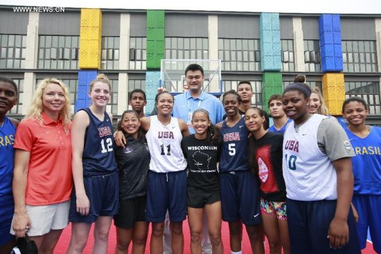 Yao Ming(C), ambassador of Youth Olympic Games poses for photos with athletes in the Youth Olympic Village in Nanjing, capital of east China's Jiangsu Province, Aug. 25, 2014. (Xinhua/Ren Zhenglai)