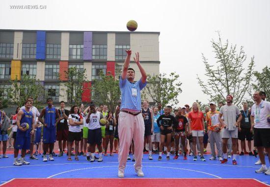 Yao Ming, ambassador of Youth Olympic Games plays basketball in the Youth Olympic Village in Nanjing, capital of east China's Jiangsu Province, Aug. 25, 2014. (Xinhua/Ren Zhenglai)