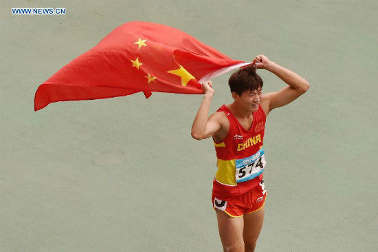 Gold Medalist Xu Zhihang of China holding the national flag of China, celebrates after the Men's 400m Hurdles Final of athletics event at the Nanjing 2014 Youth Olympic Games in Nanjing, capital of east China's Jiangsu Province, Aug. 25, 2014. (Xinhua/Ou Dongqu)