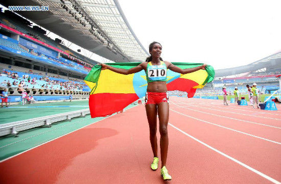 Gold Medalist Kokeb Tesfaye Alemu of Ethiopia holding her national flag, celebrates after the Women's 1500m Final of athletics event at the Nanjing 2014 Youth Olympic Games in Nanjing, capital of east China's Jiangsu Province, Aug. 25, 2014. (Xinhua/Liao Yujie)