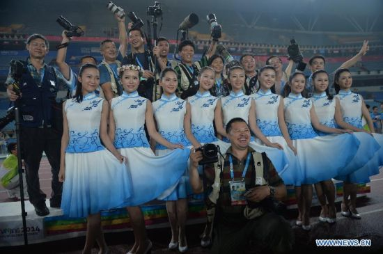 Volunteers and journalists pose for a photo together during a farewell party in the Nanjing Olympic Sports Center Stadium during the Nanjing 2014 Youth Olympic Games in Nanjing, capital of east China's Jiangsu Province, on Aug. 25, 2014. (Xinhua/Shen Peng)