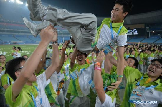 A volunteer is tossed up during a farewell party in the Nanjing Olympic Sports Center Stadium during the Nanjing 2014 Youth Olympic Games in Nanjing, capital of east China's Jiangsu Province, on Aug. 25, 2014. (Xinhua/Shen Peng)