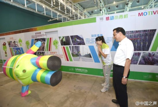 Premier Li poses with YOG mascot Lele