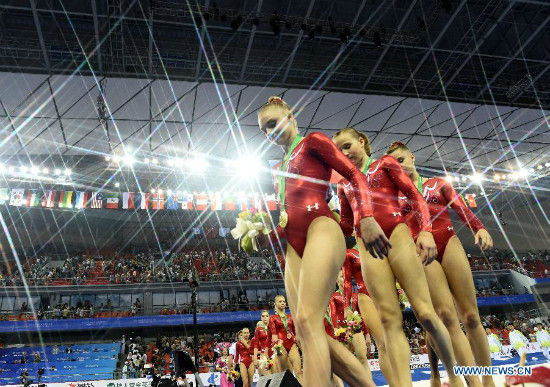 Gymnasts of team USA (front) leave the podium after the awarding ceremony of the women's team final of the 45th Gymnastics World Championships in Nanning, capital of south China's Guangxi Zhuang Autonomous Region, Oct. 8, 2014. USA team won the title with a total of 179.280 points. (Xinhua/Huang Xiaobang)