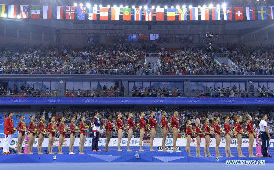 Gymnasts of Team USA (C), Team China (L) and Team Russia pose on the podium during the awarding ceremony of the women's team final of the 45th Gymnastics World Championships in Nanning, capital of south China's Guangxi Zhuang Autonomous Region, Oct. 8, 2014. Team USA team won the title with a total of 179.280 points, with China and Russia running second and third respectively. (Xinhua/Liang Xu)