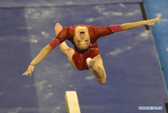 Yao Jinnan of China performs on the balance beam during the women's team final of the 45th Gymnastics World Championships in Nanning, capital of south China's Guangxi Zhuang Autonomous Region, Oct. 8, 2014. China won the silver medal with a total of 172.587 points. (Xinhua/Xiao Yijiu)