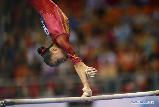 Chinese gymnast Yao Jinnan performs on the uneven bars during the women's team final of the 45th Gymnastics World Championships in Nanning, capital of south China's Guangxi Zhuang Autonomous Region, Oct. 8, 2014. China won the silver medal with a total of 172.587 points. (Xinhua/Xiao Yijiu)